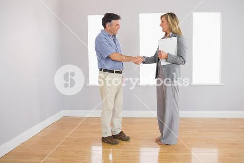 Serious realtor shaking the hand of her buyer