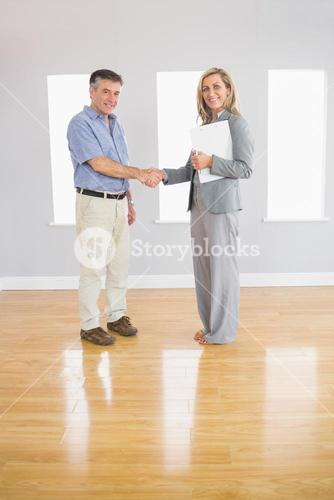Pleased realtor and buyer shaking hands