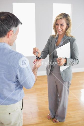 Laughing realtor holding a briefcase and giving a key to a buyer