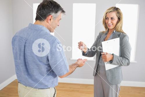 Pleased realtor holding a briefcase and giving a key to a buyer
