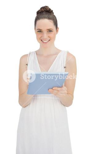 Happy young model in white dress holding tablet computer