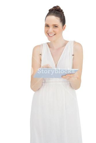 Cheerful young model in white dress using tablet computer