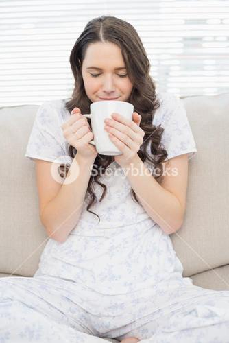Relaxed young woman in pyjamas having coffee