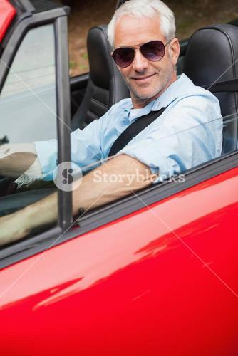 Cheerful handsome man driving his red convertible