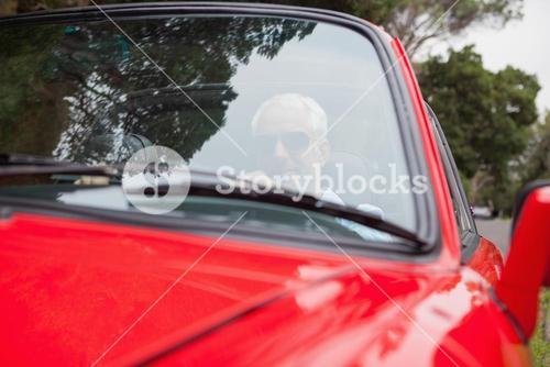 Handsome man driving red convertible