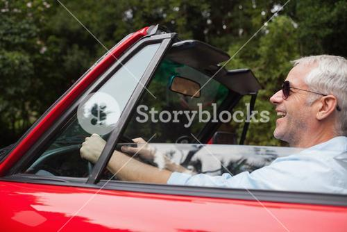 Smiling handsome man driving red convertible