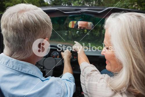 Rear view of smiling mature couple going for a ride together