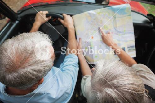 Overhead view of mature couple on holidays reading map