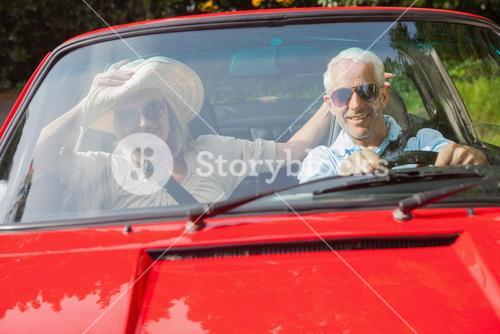 Cheerful mature couple in red cabriolet