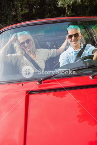 Mature couple in red cabriolet smiling at camera