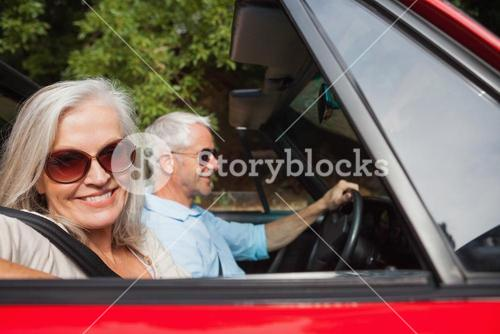 Side view of smiling mature couple driving red cabriolet