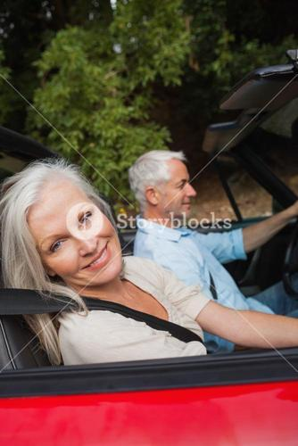 Side view of happy mature couple driving red cabriolet