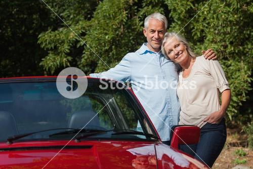 Happy mature couple hugging by their red cabriolet