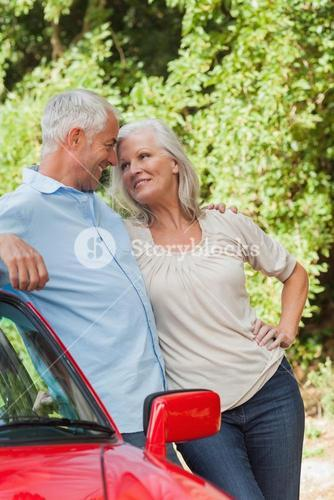 Smiling mature couple leaning against their red cabriolet