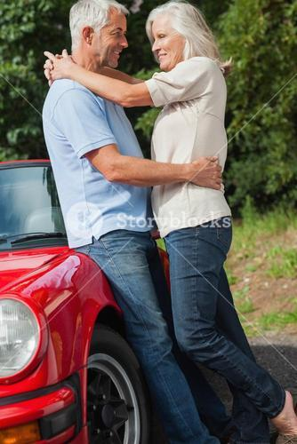 Happy mature couple hugging against their red cabriolet