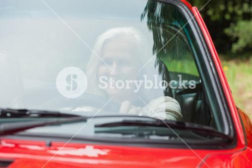 Cheerful mature woman driving red cabriolet