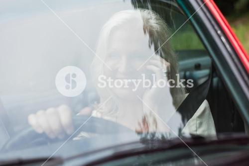 Cheerful mature woman on the phone driving red cabriolet