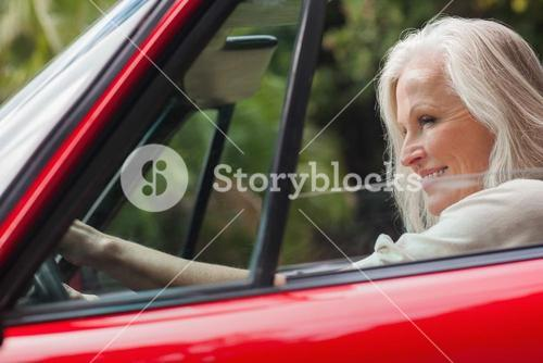 Cheerful mature woman driving red convertible