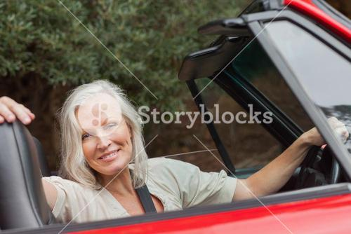 Smiling mature woman posing in red convertible
