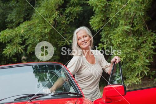 Cheerful mature woman getting off her convertible