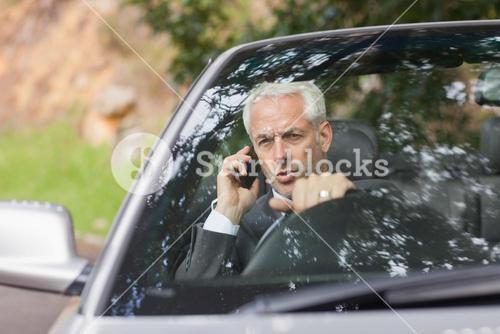 Content businessman on the phone driving expensive cabriolet