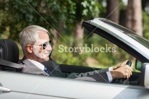 Relaxed businessman driving classy cabriolet