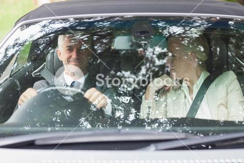 Smiling business people having a ride in classy car