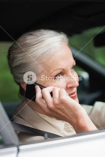 Peaceful businesswoman on the phone driving classy car