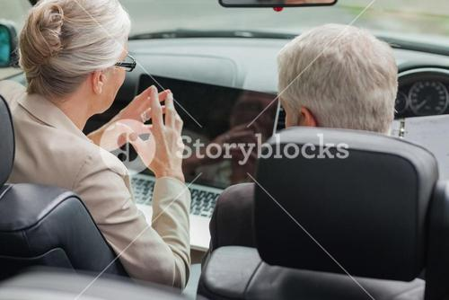 Business people working together on laptop in cabriolet