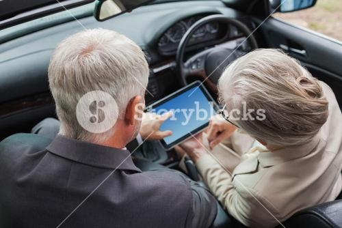 Mature partners working together on tablet in classy car