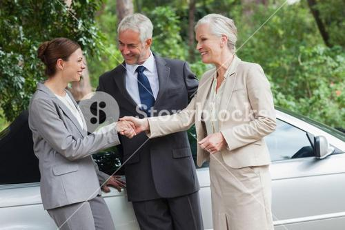 Cheerful business people talking together by classy cabriolet