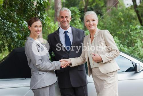 Happy business people talking together by classy cabriolet
