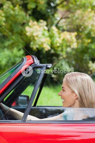 Happy woman driving red cabriolet