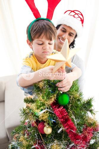 Father and son putting a star on the top of a Christmas tree