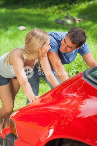 Happy couple pushing their broken down car