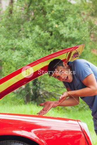 Lost young man checking his car engine after breaking down