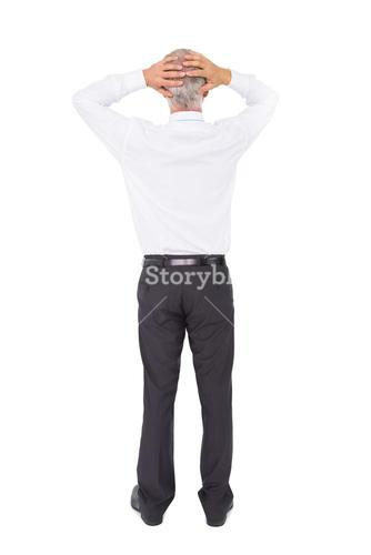 Businessman standing back to camera with hands on head
