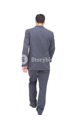 Young businessman walking away from camera