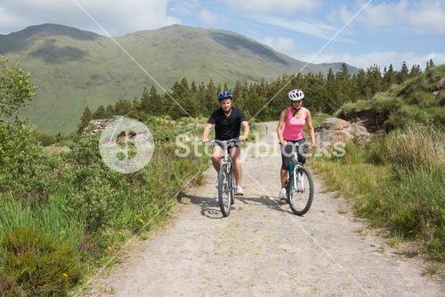 Athletic couple cycling through countryside