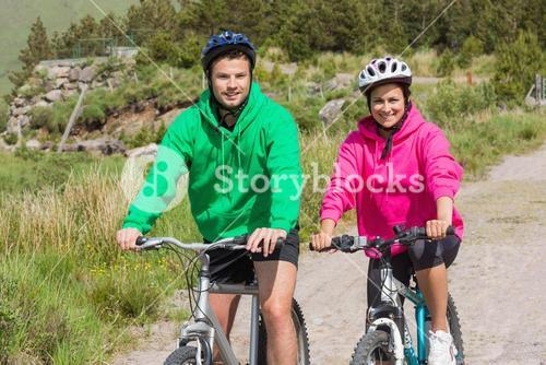 Happy couple on bike ride wearing hooded jumpers