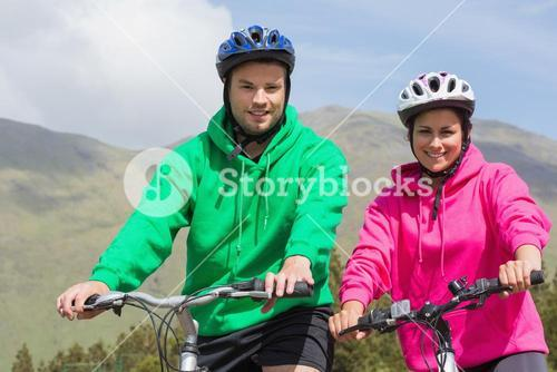 Smiling couple on a bike ride wearing hooded jumpers