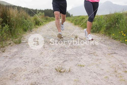 Couples feet running on trail