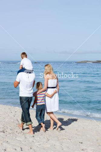 Cheerful family walking on the sand