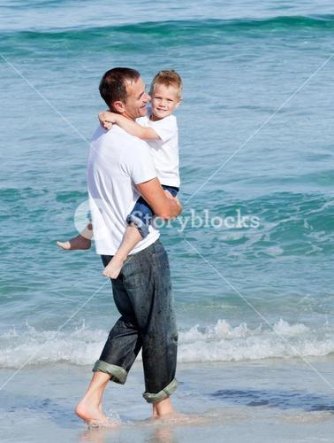 Cute little boy and his father walking on the sand