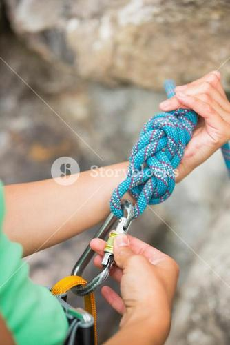 Female rock climber adjusting her harness