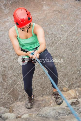 Sporty girl abseiling down rock face
