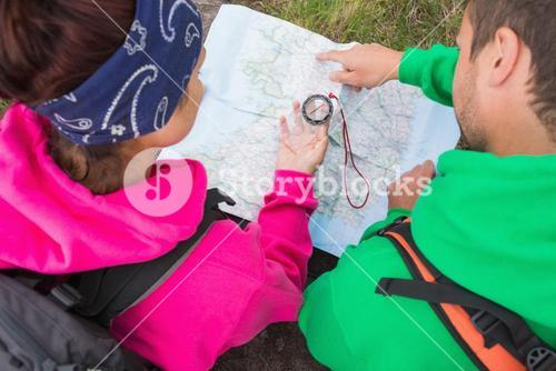 Couple using compass and map