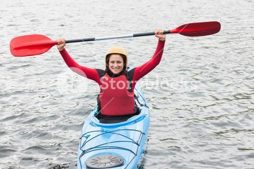 Smiling woman in a kayak cheering at the camera
