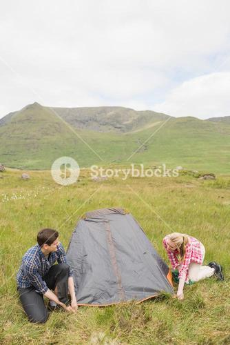 Smiling couple pitching their tent