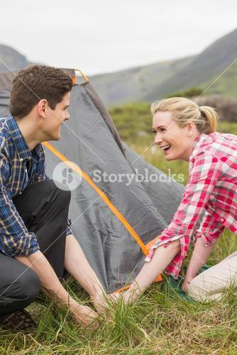 Smiling couple pitching their tent together